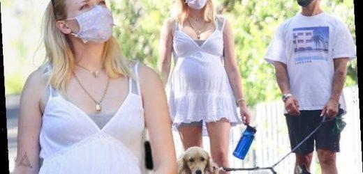 Sophie Turner cradles her baby bump in summer dress