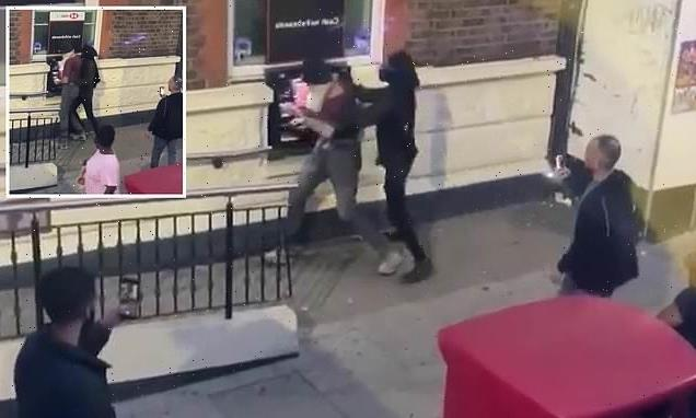 Moment two people grapple at cash machine