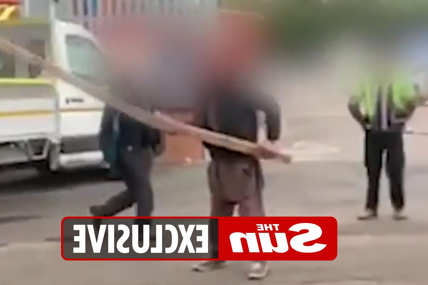 Shocking moment workers clash with planks and crowbars in massive industrial estate brawl over 'building supplies'